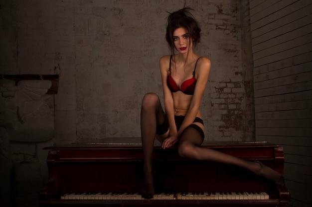 Garota de pernas longas e sexy com meias pretas e sutiã vermelho sentada em um piano em um quarto escuro