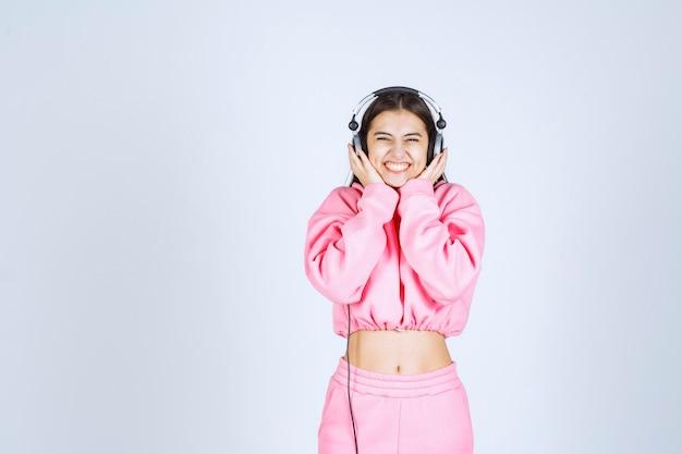 Garota de pijama rosa ouvindo os fones de ouvido e se divertindo. foto de alta qualidade