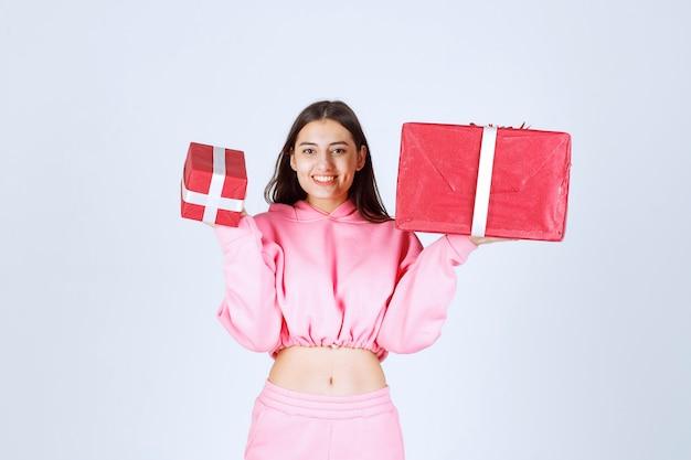 Garota de pijama rosa segurando grandes e pequenas caixas de presente vermelho e sorrindo.
