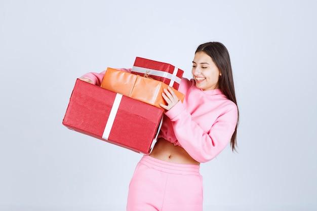 Garota de pijama rosa segurando várias caixas de presente vermelhas e se sentindo feliz.