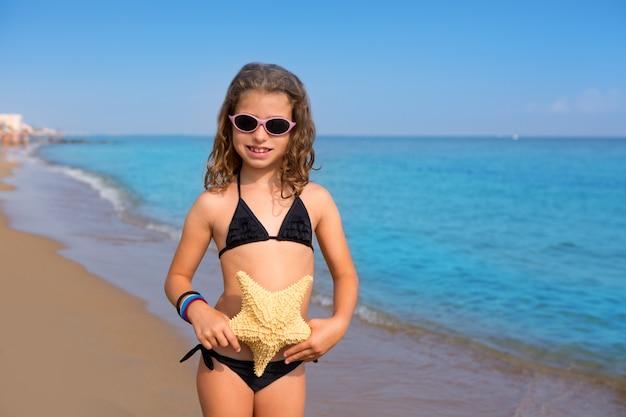 Garota de praia azul com biquíni estrela do mar e óculos de sol