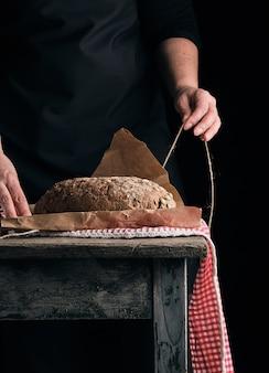 Garota de roupas pretas envolve um pão todo cozido em papel kraft marrom