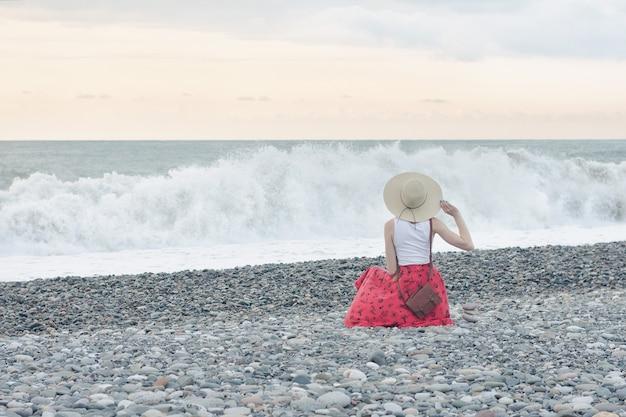 Garota de saia vermelha e chapéu senta-se à beira-mar.