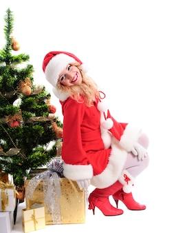 Garota de santa de natal com presentes e árvore de abeto decorada.