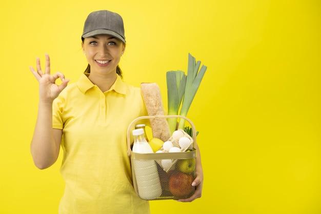 Garota de serviço de entrega de comida com cesta de compras no espaço da cópia de parede amarela