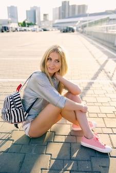 Garota de short e rabo de cavalo sentada no chão com uma mochila