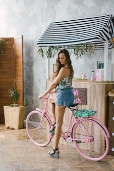 Garota de short jeans com pernas longas em uma bicicleta rosa perto do bar