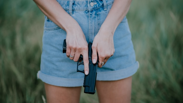 Garota de short jeans e com uma arma na mão, posando no campo.