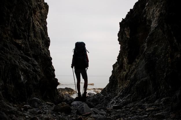 Garota de silhueta em pé entre as rochas na costa do mar com mochila de caminhadas