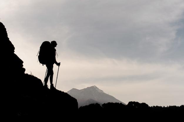 Garota de silhueta em pé nas rochas com caminhadas mochila e bengalas