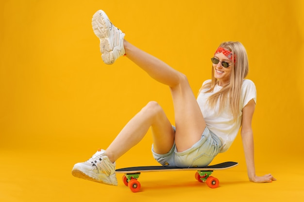 Garota de skateborder em shorts e camiseta, sentado a bordo sobre amarelo