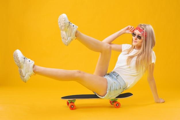 Garota de skateborder em shorts e camiseta, sentado a bordo, sobre fundo amarelo