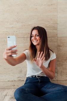 Garota de smiley vista frontal acenando para o telefone