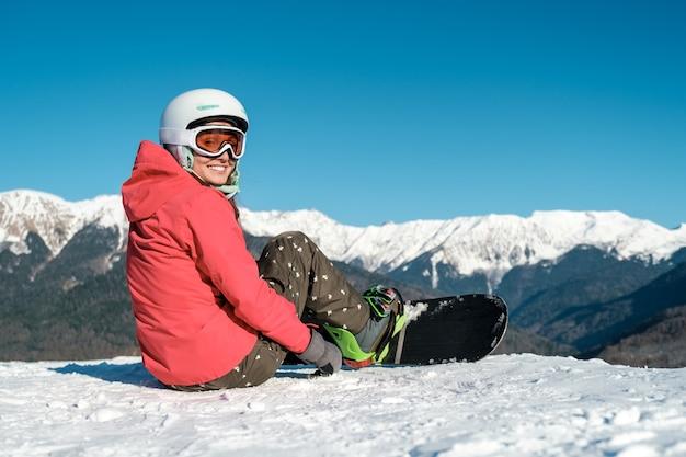 Garota de snowboarder se senta com prancha na pista de esqui nas montanhas. vista traseira. paisagem de inverno