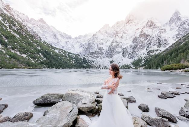 Garota de sorriso frio vestida com o vestido de noiva está de pé perto do lago das montanhas congeladas no inverno