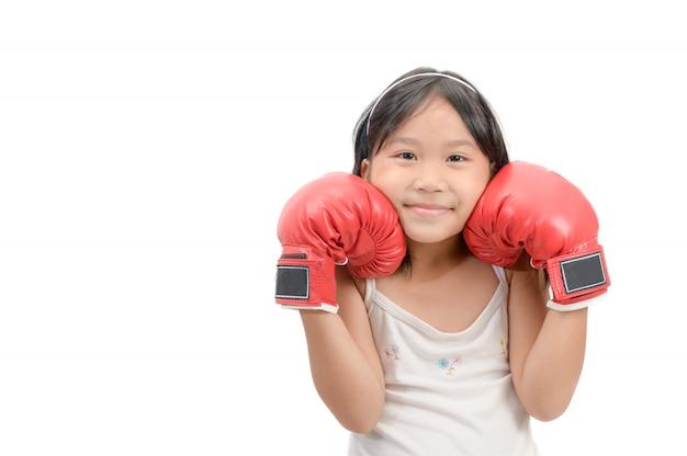 Garota de sorriso lutando com luvas de boxe vermelhas isoladas