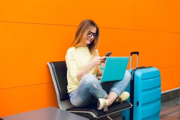 Garota de suéter amarelo e calça jeans azul está sentada na cadeira em fundo laranja. ela tem uma grande mala perto e laptop de joelhos. ela está digitando no telefone.