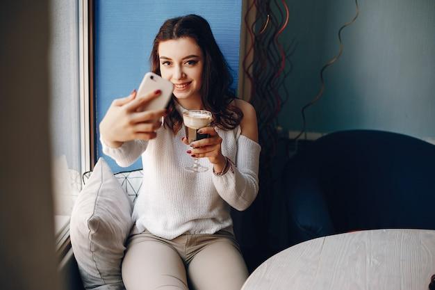 Garota de suéter branco tira uma selfie no café