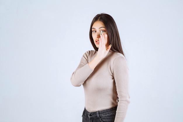 Garota de suéter cinza fofocando coisas secretas.
