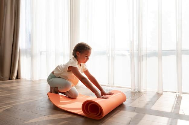 Garota de tiro completo com tapete de ioga