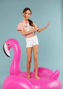 Garota de tiro completo em pé sobre um flamingo inflável
