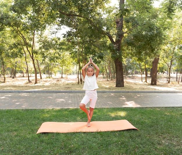 Garota de tiro completo em pé sobre uma perna na natureza