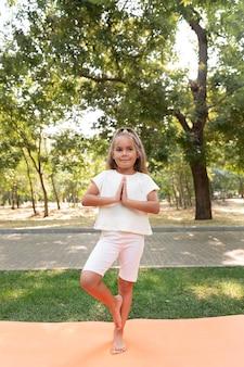 Garota de tiro completo em pé sobre uma perna