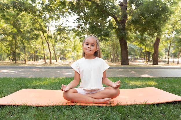 Garota de tiro completo meditando do lado de fora