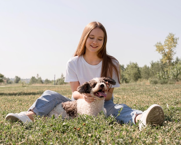 Garota de tiro completo sentada na grama com um cachorro