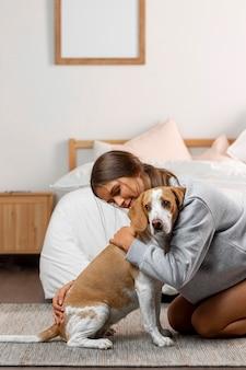 Garota de tiro médio abraçando um cachorro