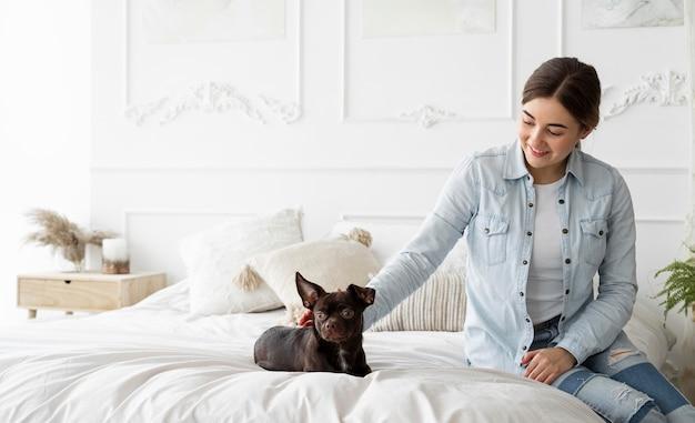 Garota de tiro médio acariciando cachorro na cama