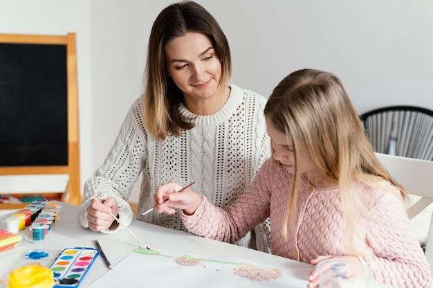 Garota de tiro médio aprendendo a pintar