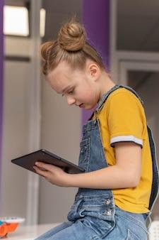 Garota de tiro médio aprendendo com tablet
