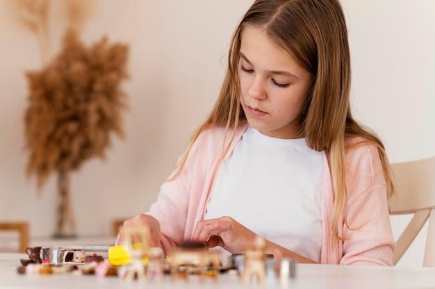 Garota de tiro médio brincando com argila dentro de casa