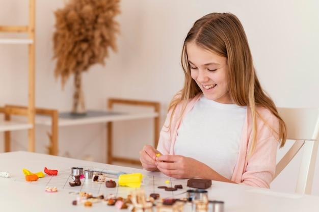 Garota de tiro médio brincando com argila
