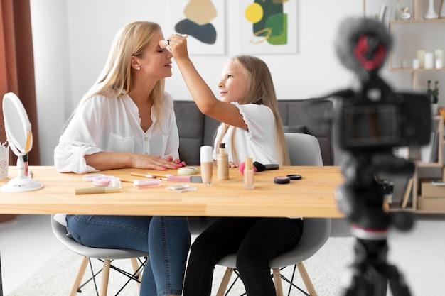 Garota de tiro médio colocando maquiagem