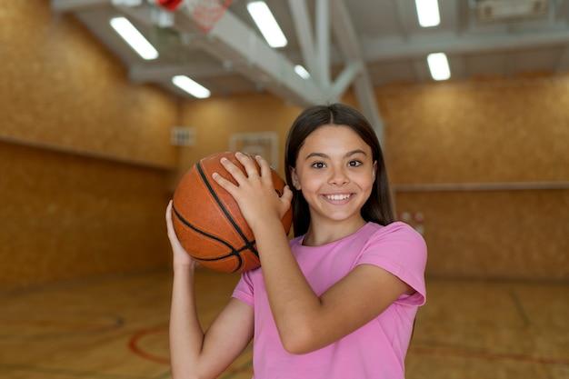 Garota de tiro médio com bola de basquete