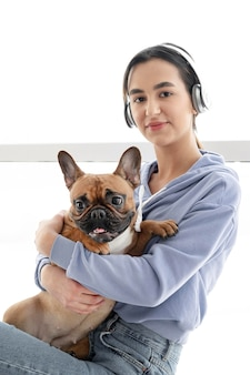 Garota de tiro médio com fones de ouvido e cachorro