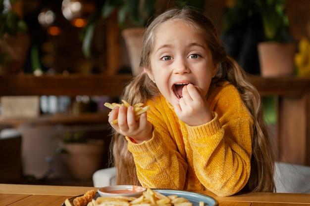 Garota de tiro médio comendo batatas fritas