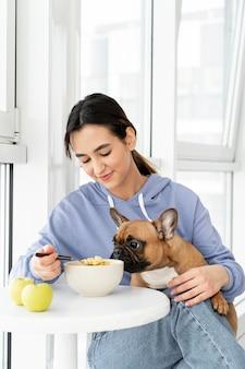 Garota de tiro médio comendo perto de um cachorro