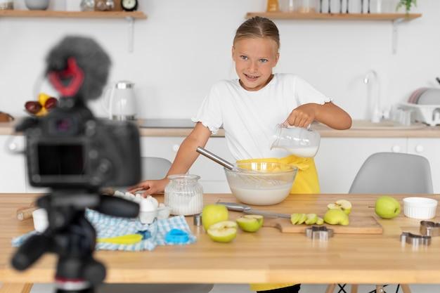 Garota de tiro médio cozinhando