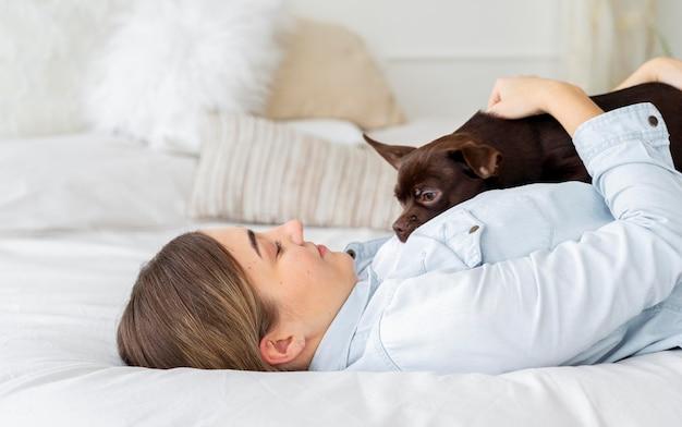 Garota de tiro médio deitada na cama com cachorro