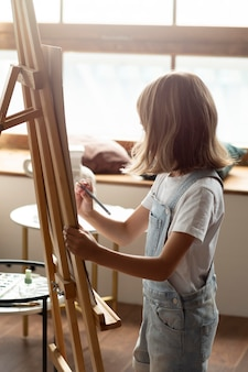 Garota de tiro médio desenhando com lápis