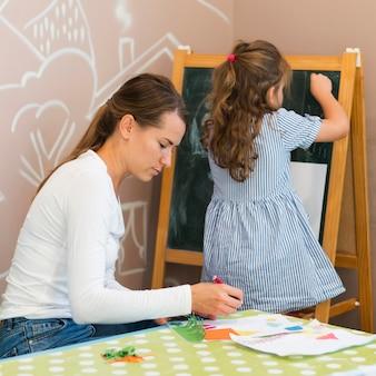 Garota de tiro médio desenhando no quadro-negro