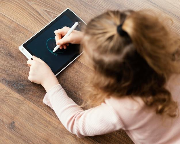 Garota de tiro médio desenhando no tablet