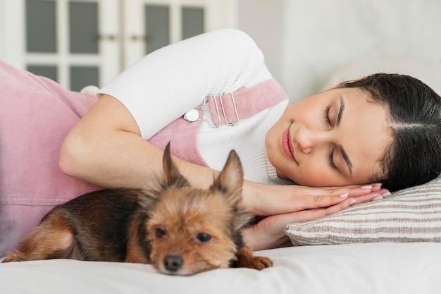 Garota de tiro médio dormindo com cachorro