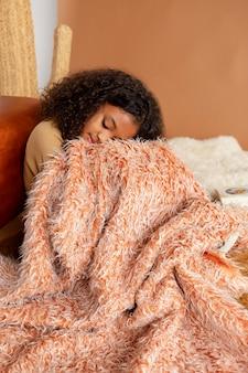 Garota de tiro médio dormindo com cobertor