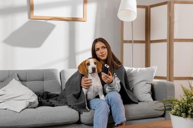 Garota de tiro médio e cachorro com controle remoto