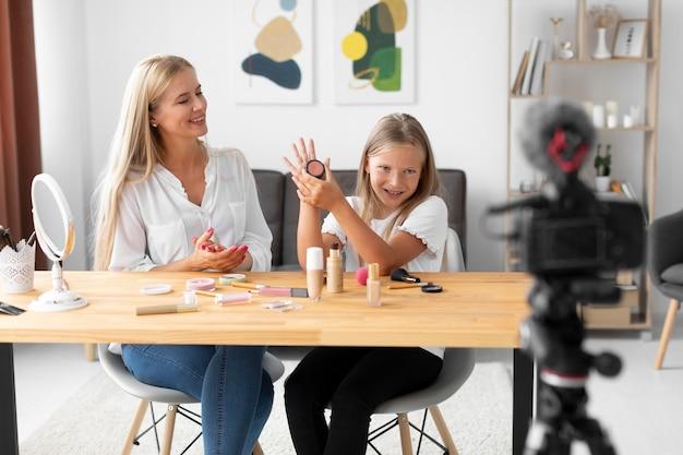 Garota de tiro médio e mulher gravando