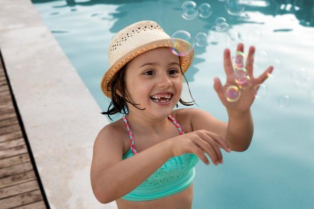 Garota de tiro médio fazendo balões de sabão na piscina